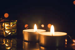Tea Light Candles burning with bokeh lights on black background.  Royalty Free Stock Photography