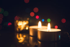 Tea Light Candles burning with bokeh lights on black background.  Stock Photography