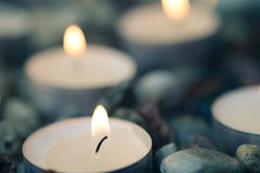 Tea-light candles on pebbles stones selective focus Stock Photo