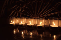 5 tea light votive candles in clear glass ironwork behind. A row of 5 votive candles, each inside clear glass container, flames reflected in varnished wood stock photos