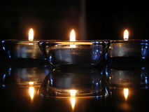 Tea Lights.... Three blue tea light candles on a black and glass table Stock Photography