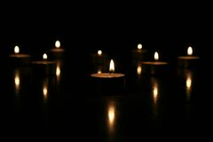 Tea lights on black background Stock Photography