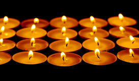 Tea lights candles with fire Stock Photos