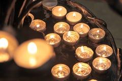 Tea lights on an iron chandelier Stock Photos