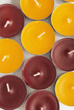 Tea lights. A lot of  yellow and maroon tea lights as a background Royalty Free Stock Photos