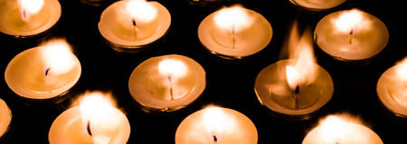 Tea lights - one grew taller. Tea lights ablaze for peace and serenity Stock Images