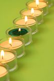 Tea lights in a row. With a green one in the row Stock Photo