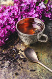 Tea and lilac. Brew tea in a stylish circle,branch of lilac on metallic background Stock Photography