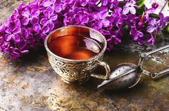 Tea and lilac. Brew tea in a stylish circle,branch of lilac on metallic background Stock Photo
