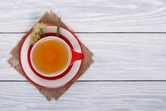Tea with lime in a red cup. On a wooden table. top view stock photography