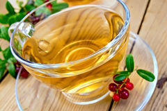 Tea with lingonberry in glass cup on board Royalty Free Stock Photos