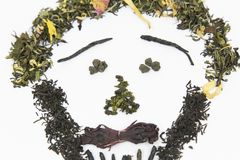 Tea of different varieties is laid out on a white background in the form of a picture - a person`s face! The image used black, gre. Tea, a lot of tea, kinds of stock images
