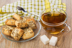 Tea, lumpy sugar, plate with cookies, napkin and teaspoon Stock Photos