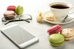 Tea with macaroons, smartphone and glasses Stock Photos