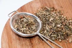 Tea made from basil with metal strainer Stock Photos