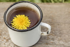 Tea made from yellow dandelion flowers taraxacum officinale in. A white enameled old cup, a spring warm day Stock Photo