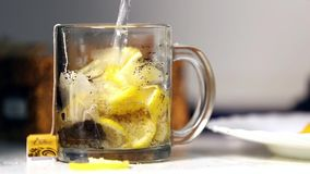 Tea and many lemons being poured into glass tea cup stock video
