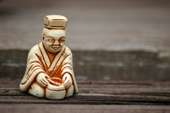 Tea Master Netsuke. Netsuke of Tea Master made of clay on a wooden background Stock Photo