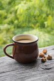 Tea with milk and biscuits on a light wooden surface against window Royalty Free Stock Image