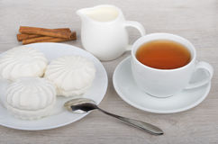 Tea, milk, cinnamon sticks and marshmallows in plate Royalty Free Stock Photos