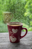 Tea with milk in the red cup, rainy day Royalty Free Stock Photos