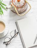 Tea with milk, teapot, notepad, glasses, pen, green flower leaf on white background, top view. Morning inspiration planning. Flat. Lay. Free space for text Royalty Free Stock Photography