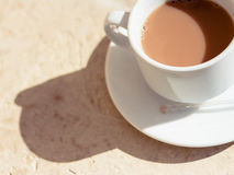 Tea with milk in a white cup in the morning sun with harsh shado. Ws on a textured wood surface. Warm tones stock images