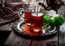 Tea with mint in the Arab style. On wooden table stock image