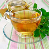 Tea with mint in cup and teapot on tablecloth Royalty Free Stock Images