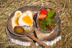 Tea with mint and strawberries in a glass. White bread with honey on the plate are on the hay Stock Image