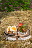 Tea with mint and strawberries in a glass. White bread with honey on the plate are on the hay Royalty Free Stock Photo