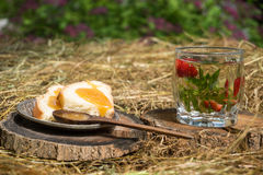 Tea with mint and strawberries in a glass. White bread with honey on the plate are on the hay Stock Photo