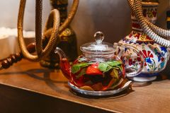 Tea with mint and strawberries in a transparent teapot. And hookahs in the restaurant Stock Images