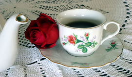 Tea in the Morning. A red rose and a cup of tea are sitting on a crocheted lace tablecloth Royalty Free Stock Images