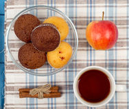 Tea, muffins, apples and cinnamon. On a napkin Stock Photography