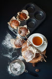 Tea and Muffins with banana, sprinkle powdered sugar. Tea and Muffins with banana, sprinkle with powdered sugar, on a black table. Selective focus. Top view Royalty Free Stock Image