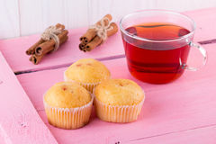 Tea with muffins and cinnamon. On a pink table Stock Photography