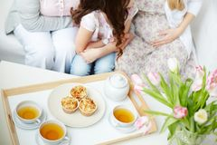 Tea and muffins. Cups of green tea and muffins on tray with little girl, her mother and grandmother sitting near by Royalty Free Stock Photography