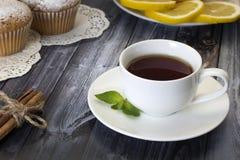 Tea , muffins , lemon and cinnamon. On the table Stock Images