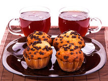 Cups of tea and muffins. Tea and muffins on a plate on white isolated Royalty Free Stock Image