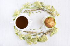 Tea and muffins on a white table. With floral decorations, light background stock photos