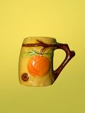 Tea mug. Fancy tea cup/mug isolated on a yellow background Royalty Free Stock Photo
