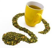 Tea mug with artfully arranged tea leaves and herbs. A peaceful and artful composition of the prepared tea and the raw herbal tea leaves to symbolize the Royalty Free Stock Image