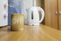Tea mug with off letters on body standing on table, copyspace Stock Photography