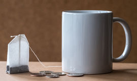 Tea and mug package. Tea mug and package with the coins passing at the table Stock Image