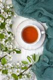Tea mug and pear flowers on wooden background Stock Photo