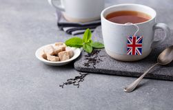 Tea in mugs with British flag tea bag label. Grey background. Copy space. stock photography
