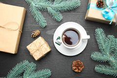 Tea and New Year`s gifts. Cup of tea and New Year`s gifts on black wooden background. Top view royalty free stock images