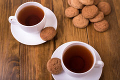 Tea and oaten cookies on a wooden table Royalty Free Stock Images