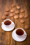 Tea and oaten cookies on a wooden table Stock Photos